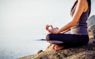 Frau meditiert am Strand foto
