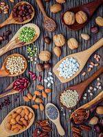 vertikale Ansicht von Hülsenfrüchten und Nüssen in Löffeln foto