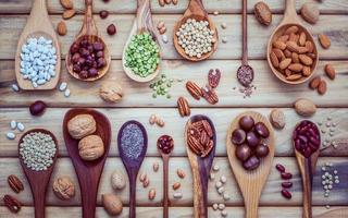 Hülsenfrüchte und Nüsse im Löffel auf hellem Holzhintergrund foto