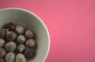 Knoblauch in einer Schüssel auf kratzendem rosa Hintergrund des Acryls foto