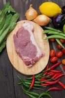 ungekochtes Steak auf Holzbrett mit Zwiebeln, Petersilie, Dill, Chilischoten, grünen Bohnen und einer Zitrone auf dunklem Holztisch