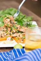 scharfer und würziger gegrillter Schweinefleischsalat auf weißem Teller auf Holztisch