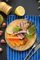 Gegrilltes Steak, Pilze und Beilagen auf Holzschneidebrett mit Karotten, Tomaten und Zitrone auf blauer Tischdecke auf dunklem Holztisch