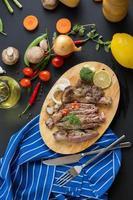 Gegrilltes Steak und Beilagen auf Holzschneidebrett mit Zwiebeln, Chilischoten, Tomaten, grünen Bohnen und einer Zitrone auf dunklem Holztisch