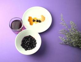 Blaubeeren, Fruchtfleisch in Sirup und Blaubeersaft auf einem lila Hintergrund