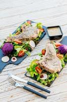 Gegrilltes Grill-Schweinekotelett-Fleischsteak auf schwarzem Teller mit Gemüse