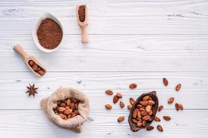 Kakaopulver und Kakaobohnen auf einem weißen hölzernen Hintergrund foto