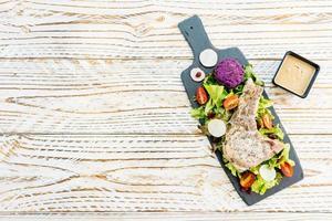 Gegrilltes Grill-Schweinekotelett-Fleischsteak auf schwarzem Teller mit Gemüse foto