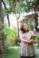glückliche junge Frau stehend und hält Notizbücher im Hausgarten