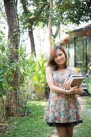 glückliche junge Frau stehend und hält Notizbücher im Hausgarten foto