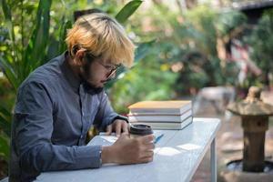 junger Hipster-Bartmann, der Kaffee trinkt, während Bücher im Hausgarten mit Natur liest foto