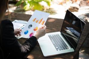 Geschäftsfrau, die mit Dokumentengraphen arbeitet und Investitionsdiagramme analysiert
