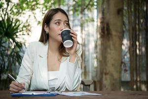 junge Geschäftsfrau, die in einem Büro sitzt und eine Tasse Kaffee trinkt foto