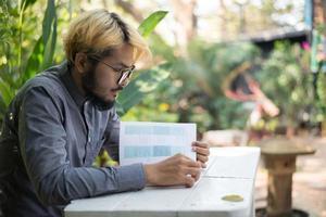 bärtiger Mann des jungen Hipsters, der Bücher im Hausgarten mit Natur liest foto