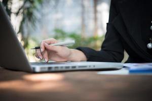 Frau arbeitet mit ihrem Laptop und Geschäftsbericht foto