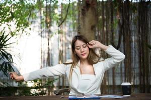 junge Geschäftsfrau streckt sich und gähnt am Arbeitsplatz foto