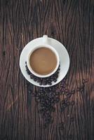 Draufsicht der Kaffeetasse und der Kaffeebohnen auf Holztisch