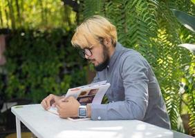 junger Hipster Bartmann, der Bücher im Hausgarten mit Natur liest. Bildungskonzept. foto