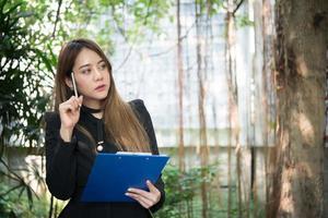 junge Geschäftsfrau, die Geschäftsdokument hält, während sie über Arbeit nachdenkt foto