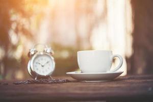 Tasse Kaffee mit Wecker auf natürlichem Morgenhintergrund