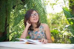 junge Hipsterfrau, die Bücher im Hausgarten mit Natur liest foto