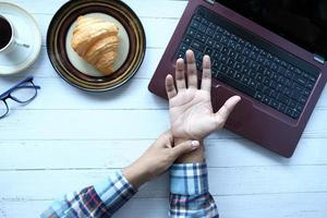 Mann, der Handgelenksschmerzen während der Arbeit am Laptop leidet