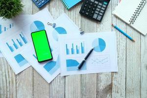 Smartphone, Taschenrechner und Notizblock auf dem Tisch foto
