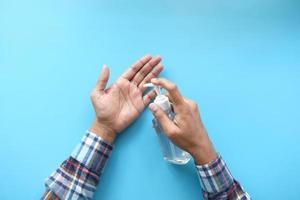Mann, der Händedesinfektionsgel auf blauem Hintergrund anwendet foto
