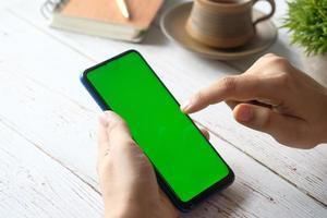 Rückansicht der Hand der Frau unter Verwendung des Smartphones foto