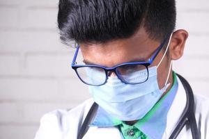 Arzt in Gesichtsmaske schaut nach unten foto