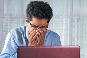 Mann niest, während er an einem Schreibtisch arbeitet foto