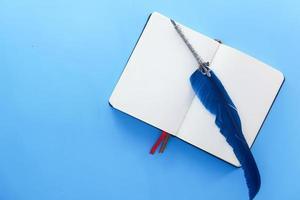 offenes Buch und alter Füllfederhalter auf blauem Hintergrund foto