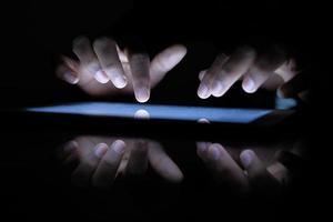 Nahaufnahme der Hände im Dunkeln tippen auf einem Tablet foto