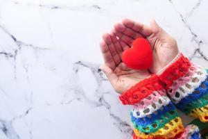 Person, die ein kleines rotes Herz hält