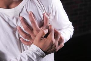 Mann umklammert die Brust vor Schmerzen