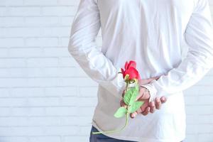 Mann hält eine Rose hinter dem Rücken
