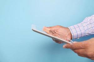 Geschäftsmann, der digitales Tablett auf blauem Hintergrund verwendet