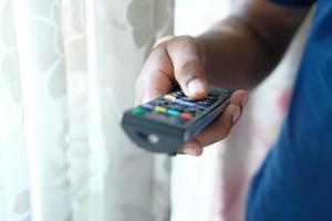 Nahaufnahme der Mannhand, die Fernsehfernbedienung hält