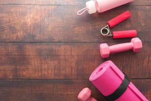 rosa Fitnessausrüstung auf hölzernem Hintergrund