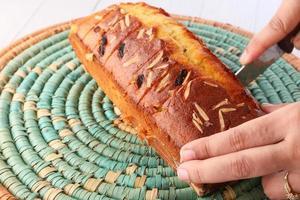 Frauenhand, die einen Kuchen auf dem Tisch schneidet