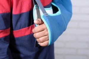 junger Mann, der eine Armschlinge für gebrochenen Knochen trägt foto
