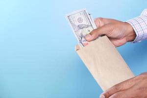 Person, die große Rechnungen in eine braune Tasche steckt