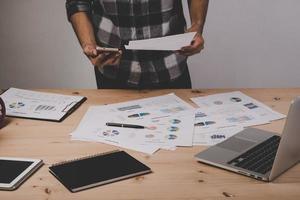 Nahaufnahme des Geschäftsmannes, der mit Strategiediagrammen auf Holzschreibtisch im Büro arbeitet