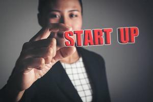 Geschäftsfrau, die Startwortbrief gegen Hintergrund hält foto
