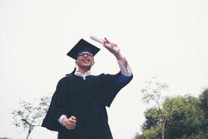 glücklicher Doktorand, der ein Diplom in der Hand hält foto