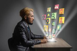 junger Geschäftsmann im Büro mit modernen digitalen Medien 3d Ikonen foto
