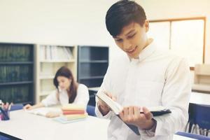 junge asiatische Studenten in der Bibliothek lesen ein Buch foto