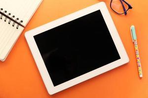 flache Zusammensetzung des digitalen Tabletts und des stationären Büros auf orangefarbenem Hintergrund foto