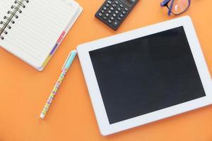 flache Zusammensetzung der digitalen Tablette auf orange Hintergrund foto