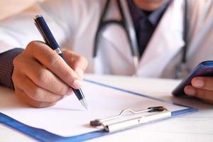 Arzthände schreiben ein Rezept foto